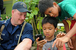 US_Navy_110506-N-SP676-176_Mineman_3rd_Class_Matt_Miller_gives_children_his_smart_phone_to_play_with